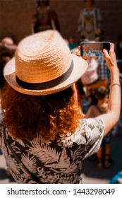 Tourist girl with straw sunhat taking a picture of Giants and large heads in a traditional festival in Solsona, Spain.