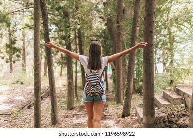 tourist girl with a striped backpack spreads her arms in the forest