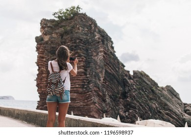 tourist girl takes picture of a puff mount on the phone