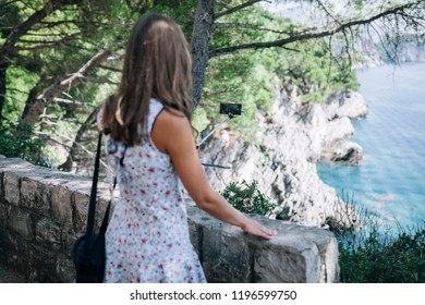 tourist girl takes pictures of a beautiful landscape