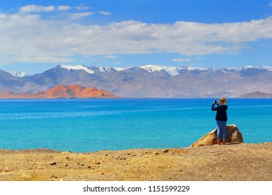 Tourist girl taking pictures of mountain landscape on phone while traveling