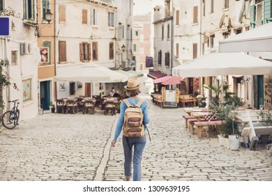 Tourist girl walking in the city during vacation. Cheerful woman traveling abroad in summer. Travel and active lifestyle concept