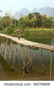Tourist girl walking on bamboo bridge, vang vieng, laos