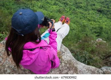 Tourist girl wearing a shirt Pink sits on a cliff overlooking green trees in the rainy season, adventure travel and nature walks. Popular in the National Park of Thailand.
