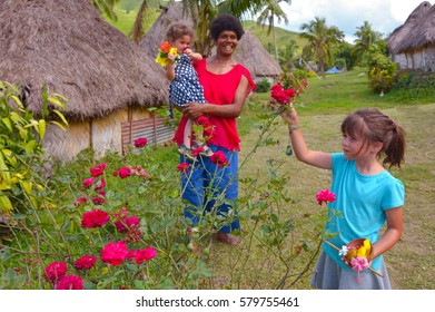 Tourist girls (age 3 and 6 ) interact with Indigenous Fijian woman and pick up flowers during a visit in Navala village on the highlands of  Viti leavu island, Fiji. Real people