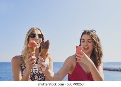 Tourist girls taking photos of ice cream eating on beach using smart phone technology on adventure travel