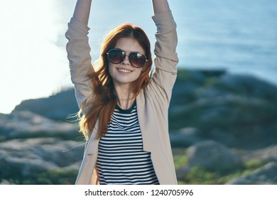 Tourist with glasses with hands up in the mountains