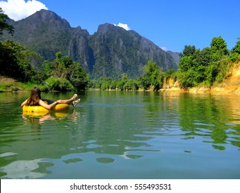 Tourist going down Nam Song River in a tube surrounded by karst scenery in Vang Vieng, Laos. Tubing is a popular tourist activity in Vang Vieng.