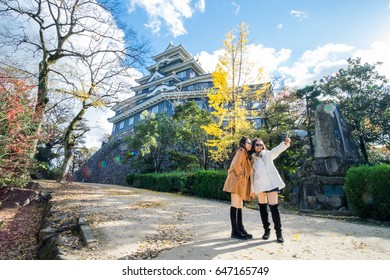 Tourist groups Selfie at Okayama castle In the morning. Travel Japan , Japanese castle with sun flare