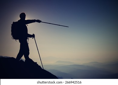 Tourist guide show right way with pole in hand. Hiker with sporty backpack stand on rocky view point above  misty valley. Sunny spring daybreak in rocky mountains. Mountain adventure guide. Man hike