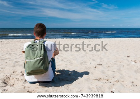 A tourist guy with a backpack on the Baltic Sea coast near Tallinn enjoys  nature in 922970f9c429e