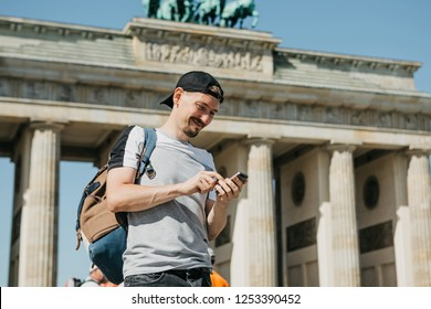 A tourist or a guy with a backpack uses a mobile phone to call or see a map or get online.