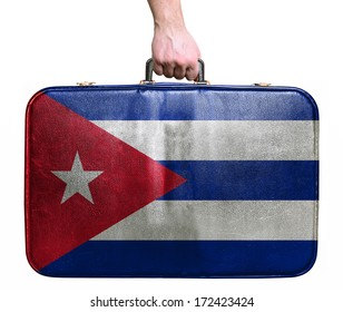 Tourist hand holding vintage leather travel bag with flag of Cuba
