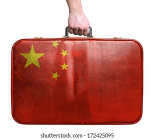 Tourist hand holding vintage leather travel bag with flag of China