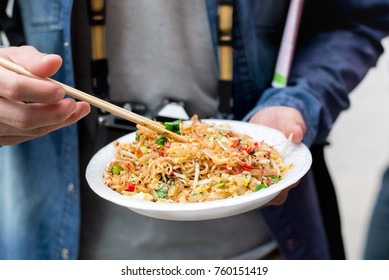Tourist hands holding Pad Thai, one of famous traditional Thailand street food, with chopsticks about to eat while traveling in Bangkok