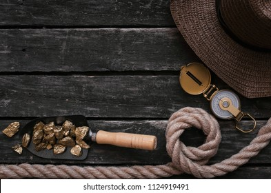 Tourist hat, shovel full of gold ore, compass, rope on aged wooden table background. Treasure hunter concept. Adventurer accessories.