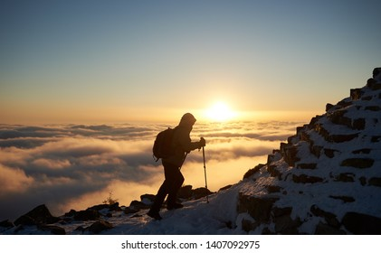 Tourist hiker with backpack climbing up on rocky mountain steep slope covered with first snow on background of foggy valley filled with white puffy clouds, raising sun and bright blue sky at dawn.
