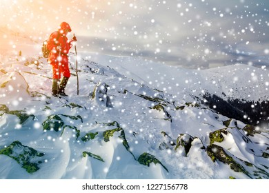 Tourist hiker in bright red clothing with walking sticks descending dangerous rocky mountain slope covered with snow on stormy cloudy sky copy space background.
