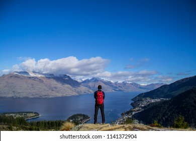 Tourist hiker man standing on the top of the mountain. Enjoying landscape scenic/panorama view of lake Wakatipu, mountains and Queenstown. South Island, New Zealand. Travel/outdoor/tourism concept.
