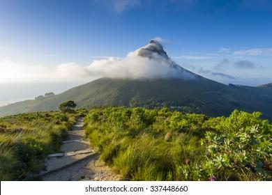 Tourist hikers up Cape Town, Table Mountain landscape, overlooking Lions Head peak
