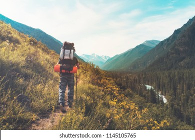 Tourist with hiking backpacks in mountain hike on summer day. Tourist in beautiful mountain landscape. Young guy go along the footpath through the mountains of Altay.