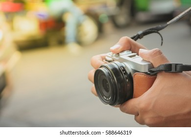Tourist hold digital camera (mirrorless camera) ready for take a photo