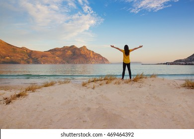 Tourist holding arms up in the air at Hout Bay beach at dusk