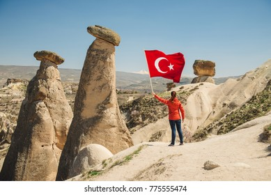 Tourist holding turkish national flag close to mushroom-like fairy chimneys on a sunny day