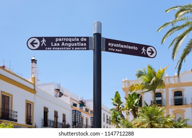 Tourist information sign in Ayamonte, Andlaucia, Spain indicating the direction to the city hall, or town hall and the local church. It is written in English and Spanish