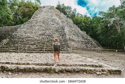 Tourist in the jungle with a backpack and a hat. Tourism in the ancient city Mayan pyramids