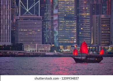 Tourist junk boat ferry with red sails and Hong Kong skyline cityscape downtown skyscrapers over Victoria Harbour in the evening. Hong Kong, China