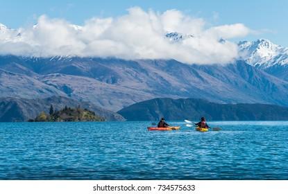 Tourist kayaking in lake Wanaka the fouth largest lake in New Zealand.
