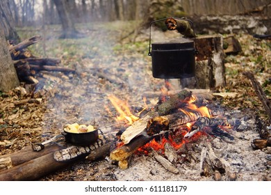 Tourist kettle on camp fire with tent on background. hand with stick about fire.