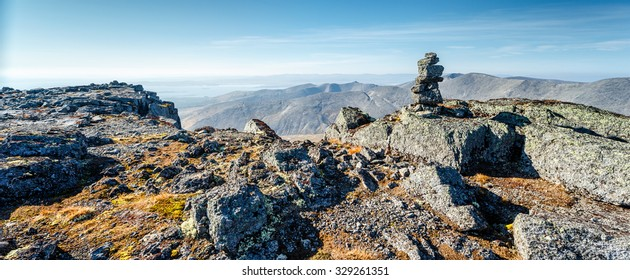 Tourist landmark made of rocks on top of Judychvumchorr plateau in Hibiny mountains with a view on neighboring mountains and Large Imandra lake, Kola peninsula above the Arctic circle, Russia