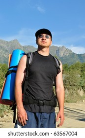Tourist with a large backpack is a high mountain, on the way, full-face photos