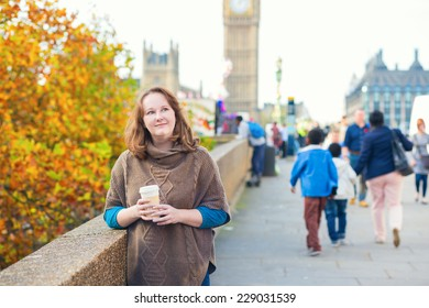 Tourist in London walking on the street and drinking coffee