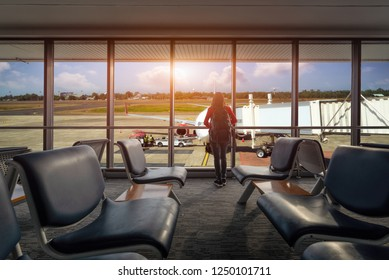 tourist is looking at flying plain in sky. she is standing near window at airport