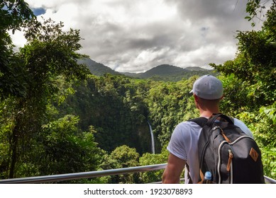 Tourist looking at the La Fortuna Waterfall in Costa Rica. The waterfall is located on the Arenal River at the base of the dormant Chato volcano.