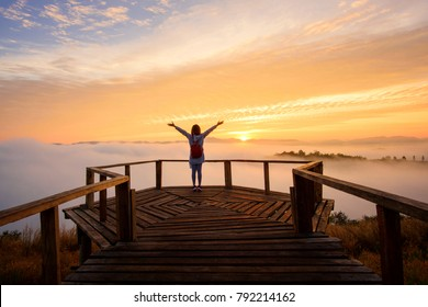 Tourist looking at landscape sea of misty on walkway wood bridge in dawn morning sunrise time at phu lam duan, Loei province,Thailand