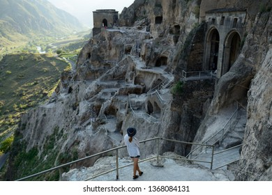 Tourist looking on the Vardzia cave monastery and ancient city in mountain rocks, one of the main attraction in Georgia, UNESCO