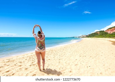Tourist looking at the sea and making heart gesture, on the beach of Arraial D'Ajuda, in Porto Seguro, Bahia. Beautiful beach located in Brazil. Woman looking out to sea during vacation.