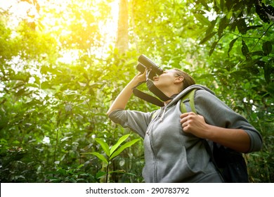 Tourist looking through binoculars considers wild birds in the jungle.Bird watching tours