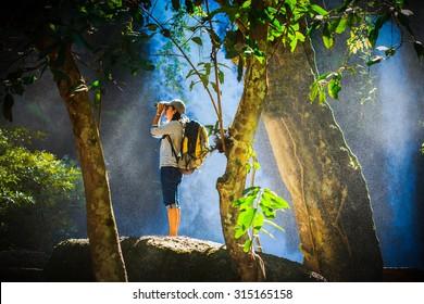 Tourist looking through binoculars considers wild birds in the Khaoyai national park Thailand, water spray spreading around her