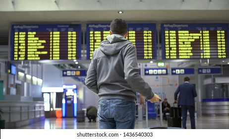 Tourist looking at time table, checking schedule on screen in bus terminal