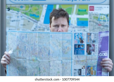 A tourist is lost and searching his way with a map