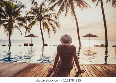 tourist in luxury beach hotel near luxurious swimming pool at sunset, getaway, tropical exotic holidays vacation, tourism and travel