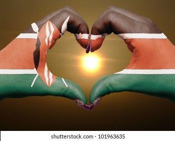 Tourist made gesture  by kenya flag colored hands showing symbol of heart and love during sunrise