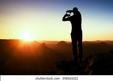Tourist make frame with palms and fingers on both hands. Hiker stand on rocky view point, daybreak in rocky mountains.