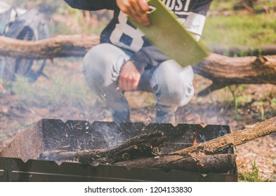 A tourist makes a fire in the brazier during a stop in the forest