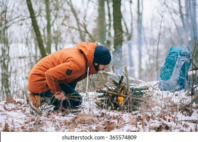 a tourist is making camp fire in the winter woods